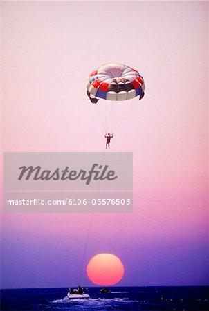 Man parachuting over sea at sunset,