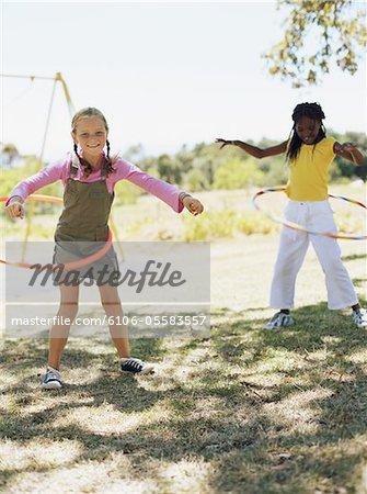 Deux filles (8-10) arceaux en plastique autour de taille à l'extérieur de majorette