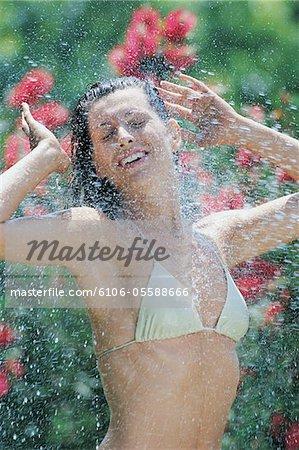 Seitenansicht einer jungen Frau in einem Bikini Top wird spritzte mit Wasser