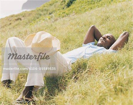 Jeune homme trouve sur une colline herbeuse avec ses mains derrière la tête