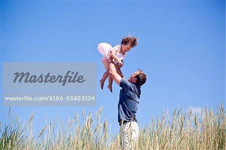 Ein Vater und Tochter spielen im Freien.