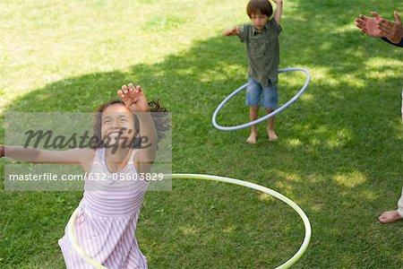Mädchen spielen mit Kunststoff-Reifen