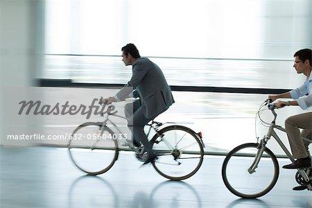 Les hommes d'affaires d'équitation bicyclettes à l'intérieur, silhouette, flou de mouvement