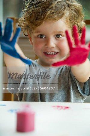 Kleiner Junge mit den Händen bedeckt in Farbe