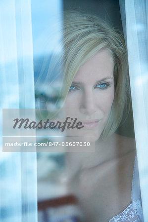 Femme avec une expression triste, une fenêtre de