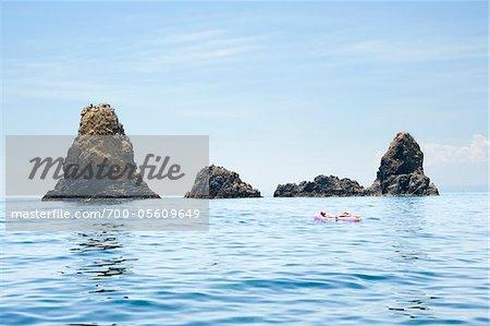Frau auf Floatation Gerät, Aci Trezza, Provinz Catania, Sizilien, Italien