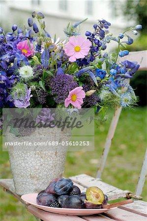 Bouquet de fleurs d'été et les prunes sur chaise de jardin