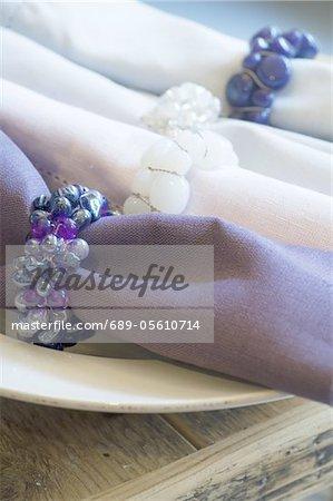 Vier Servietten mit Ringen auf Platte