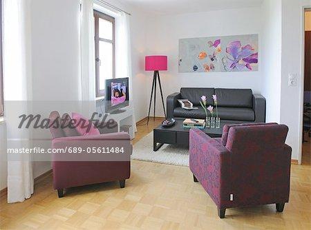 Modernen Wohnzimmer mit Malerei und Blumen auf dem Tisch