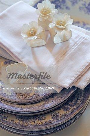 Blüten und Servietten Stapel von Platten
