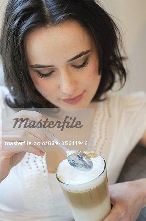 Jeune femme buvant Latte Macchiato