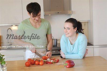 Jeune couple dans la cuisine pour trancher les légumes