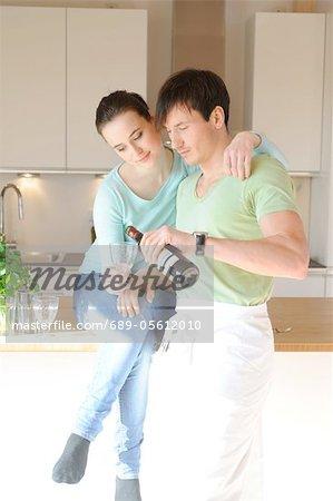 Jeune couple, boire du vin rouge dans la cuisine