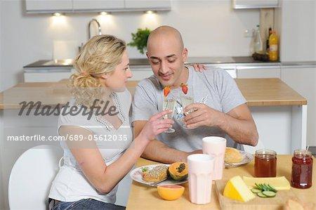Verres à champagne tintements d'heureux couple dans la cuisine