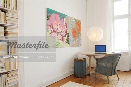 Zimmer mit Bücherregal, Gemälden und Laptop auf Tisch