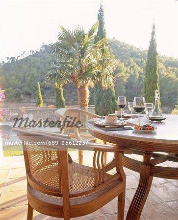 Table sur la terrasse avec les tasses et verres à vin