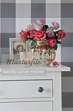 Bouquet de roses, de photographie et de bougies sur la commode