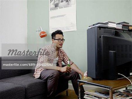 Homme, regarder la télévision avec bière et croustilles