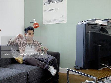 Mann mit Bier und Chips vor dem Fernseher