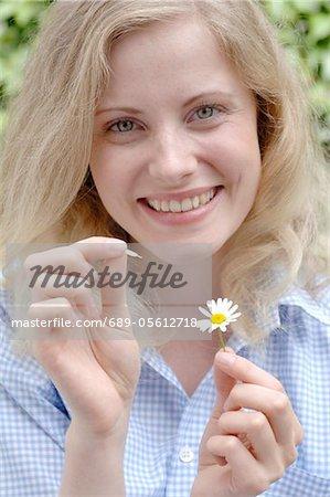 Femme heureuse plumaison pétales de marguerites