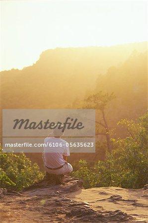 Teenager (15-17) beobachten Sonnenuntergang über Hügel, Rückansicht