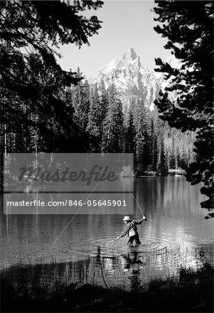 1960s MAN FISHING HOLDING NET AND ROD WYOMING GRAND TETON NATIONAL PARK STRING LAKE