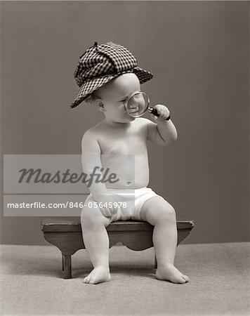 1940s BABY SHERLOCK HOLMES IN DIAPER SITTING ON BENCH WEARING DEER STALKER HAT LOOKING THROUGH MAGNIFYING GLASS
