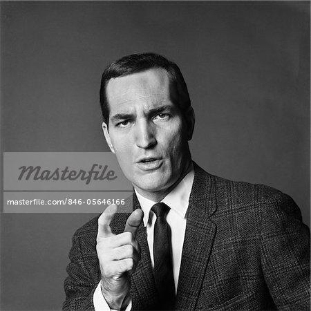 ANNÉES 1960 BUSINESS MAN EN COLÈRE EXPRESSION FACIALE POINTANT SON DOIGT