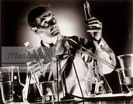 1930s SCIENTIST CHEMIST HOLDING UP TEST TUBE VIAL BEAKER IN LABORATORY