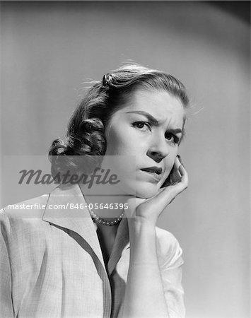 ANNÉES 1950 - ANNÉES 1960 FEMME PORTRAIT INQUIET FACIALE EXPRESSION MAIN À JOUES DENT DOULEUR