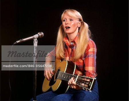 ANNÉES 1970 BLONDE JEUNE FEMME PONYTAILS PLAID SHIRT JEANS JOUE GUITARE MICRO CHANT CHANTEUR FOLK SINGERS
