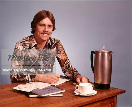 ANNÉES 1970 JEUNE HOMME MOUSTACHE FORT PRINT SHIRT TASSE À CAFÉ VIDE BUREAU POT TRAVAILLANT SUR LE BUDGET FAMILIAL, REGARDANT LA CAMÉRA