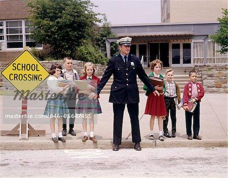 GROUPE DES ANNÉES 1960 HOMME TRAFIC POLICIER HOLDING BACK DES ÉLÈVES DU PRIMAIRE EN ATTENTE EN BORDURE DE RUE JUSQU'À LA RUE DE LA CROIX EN FACE DE L'ÉCOLE