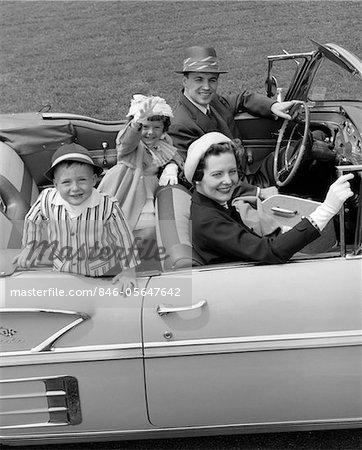 ANNÉES 1950 SOURIANT FAMILLE PORTRAIT PÈRE MÈRE FILS FILLE AUTOMOBILE DÉCAPOTABLE CHEVROLET