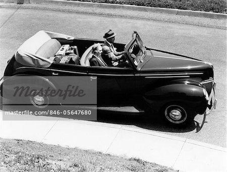 ANNÉES 1930 - ANNÉES 1940 COUPLE MARI ET FEMME AU VOLANT 1938 CABRIOLET QUATRE PORTES BERLINE AUTOMOBILE AVEC BANQUETTE ARRIÈRE EN BAGAGES