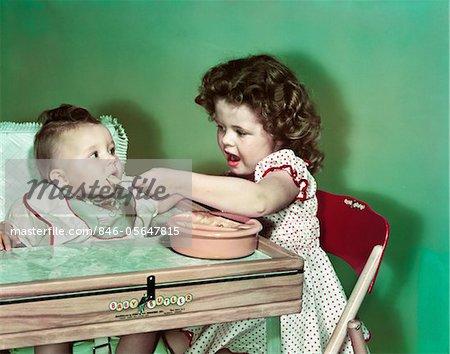 ANNÉES 1940 - ANNÉES 1950 FILLE ASSISE ALIMENTATION BÉBÉ SŒUR EN CHAISE HAUTE