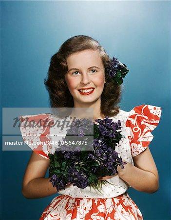 ANNÉES 1940 - ANNÉES 1950 SOURIANTE JEUNE FEMME PORTANT DES ROUGE ET BLANC ROBE HOLDING BOUQUET DE VIOLETTES