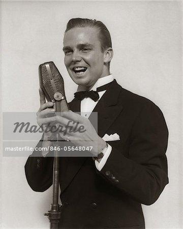 1920s - 1930s SMILING MAN RADIO SINGER ENTERTAINER CROONER IN TUXEDO SINGING INTO MICROPHONE