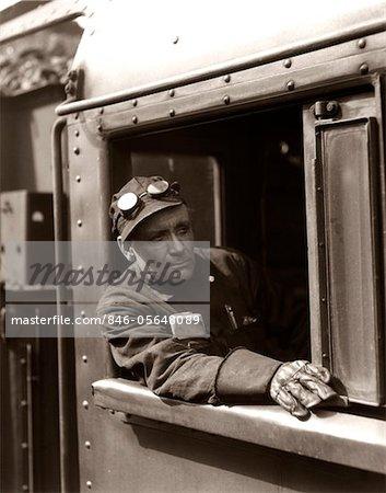ANNÉES 1920 - ANNÉES 1930 - ANNÉES 1940 RAILROAD TRAIN INGÉNIEUR REGARDANT PAR LA FENÊTRE DE LA CABINE DE LA LOCOMOTIVE CONDUIRE LA MACHINE À VAPEUR