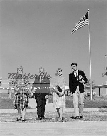 ANNÉES 1960 GROUPE 4 LYCÉENS EN PASSANT DEVANT LE DRAPEAU AMÉRICAIN TRANSPORTANT DES MANUELS
