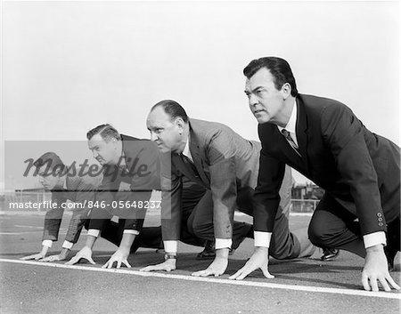 ANNÉES 1960 QUATRE HOMMES D'AFFAIRES SUR LA LIGNE DE DÉPART