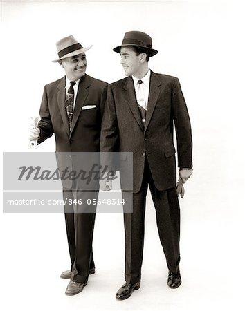 1950s TWO MEN SALESMAN BUSINESSMAN BUSINESS SUIT TIE HAT SMILING WALKING TALKING SIDE BY SIDE