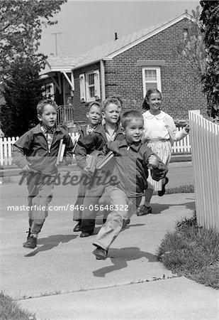 GROUPE DES ANNÉES 1950 DES ENFANTS D'ÂGE SCOLAIRE EN COURS D'EXÉCUTION AU COIN DU QUARTIER SUBURBAIN EN PALISSADE