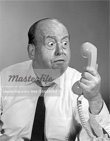 ANNÉES 1960 - ANNÉES 1970 HOMME CALVITIE EN COLÈRE ONT ACCÈS AUX YEUX EXORBITÉS RÉCEPTEUR TÉLÉPHONIQUE