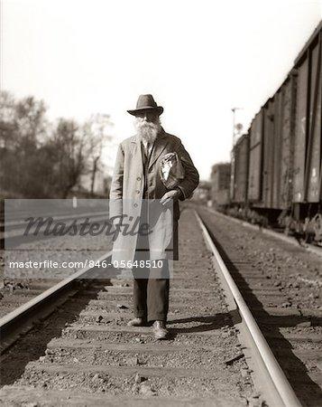 1930s GREAT DEPRESSION ERA MAN HOMELESS HOBO WALKING DOWN RAILROAD TRACKS
