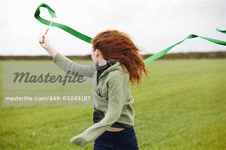 Teenage girl playing with ribbon