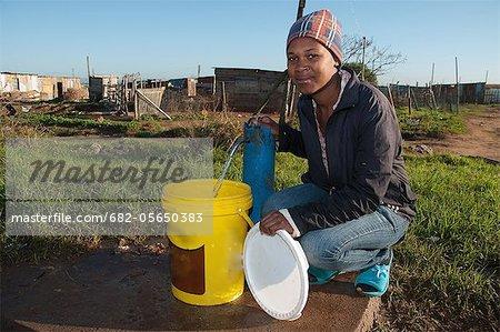 Junge Frau am Waterpoint in Town, Missionvale, Port Elizabeth, Provinz Ostkap, Südafrika