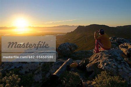 Jeune femelle adulte assis sur rocher sur sunrise regarder top montagne vallée plat dessous, Table Mountain National Park, Cape Town, Western Cape, Afrique du Sud