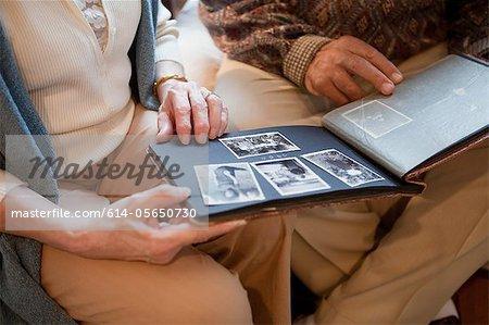 Senior couple looking through photo album, mid section