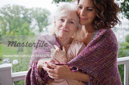 Haute femme et fille embrassant sur porche, portrait